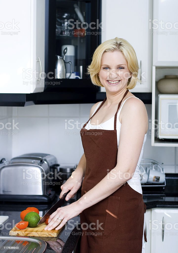 young blond woman preparing food in the kitchen royalty-free stock photo