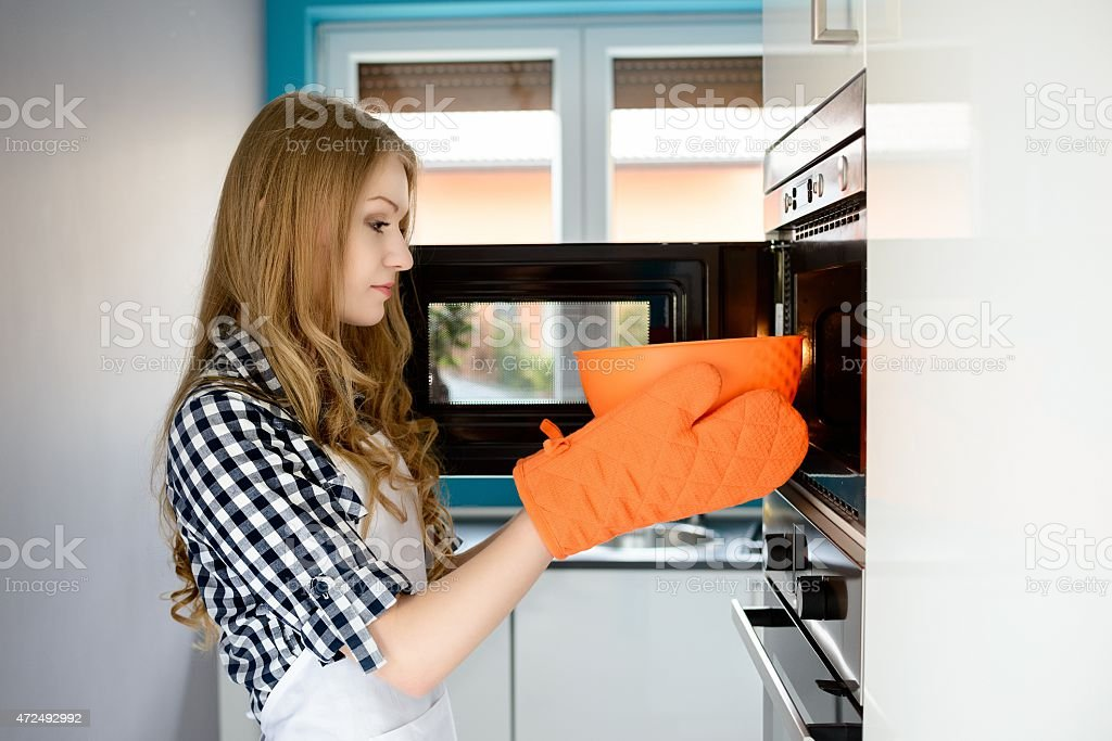 Young blond woman pulls out a hot bowl of  microwave stock photo