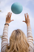 Young blond woman throwing a blue ball into the sky. Closeup of a woman playing volleyball on the sunny simmer day. Outdoors. Hands and ball.