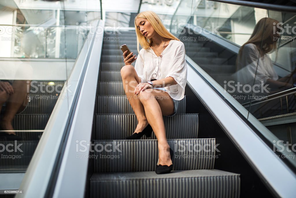 Young blond woman using smart phone on escalator. foto de stock royalty-free