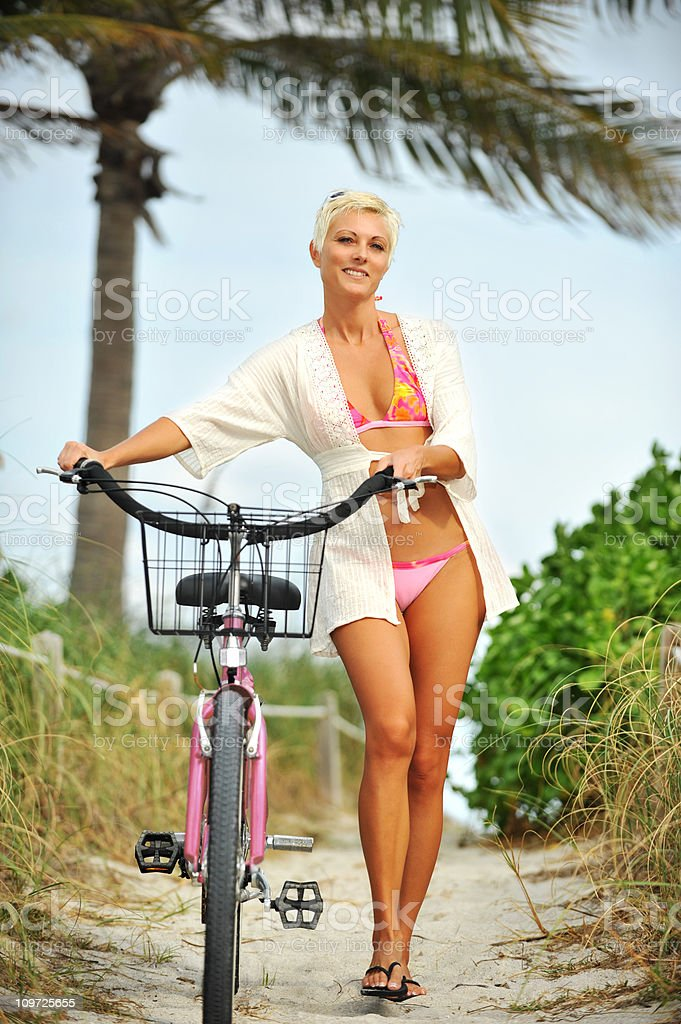 Young Blond Woman walking Bicycle at beach wearing coverup royalty-free stock photo