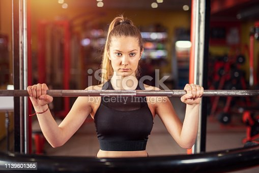 Young blond woman who is preparing for squat training in gym, looking with a motivating look