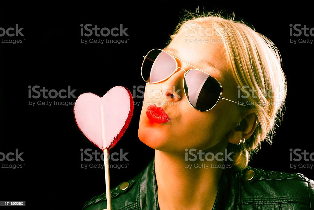 Young blond woman with heart lollipop stock photo