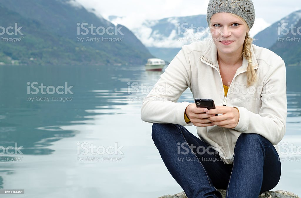 young blond woman with her Smartphone in the hand royalty-free stock photo