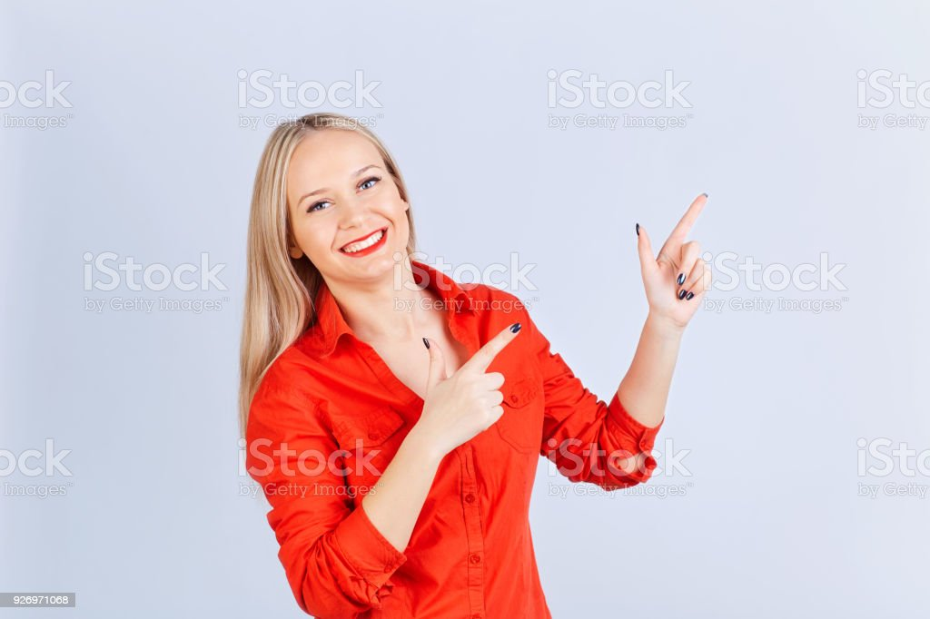 Young blond woman , with positive emotions points to a gray back stock photo