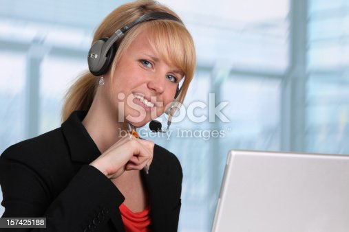 istock Young blond woman working with computer and headset 157425188