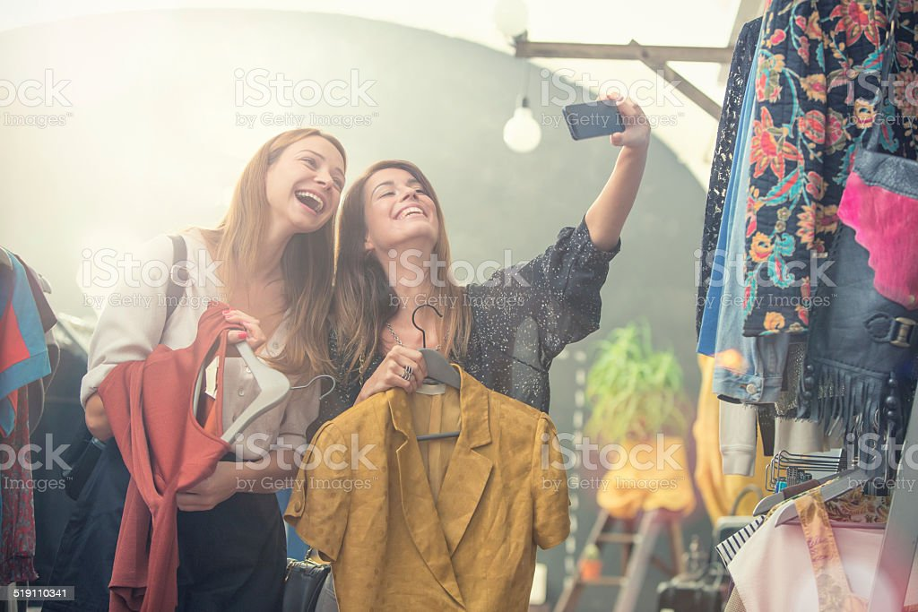 Young blonde and brown friends enjoy in secondhand clothing shop​​​ foto