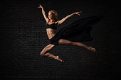 Young blonde ballerina in sportswear underwear dances and jumps in a studio with black brick on the background. modern ballet performance. Perfect fitness woman body.