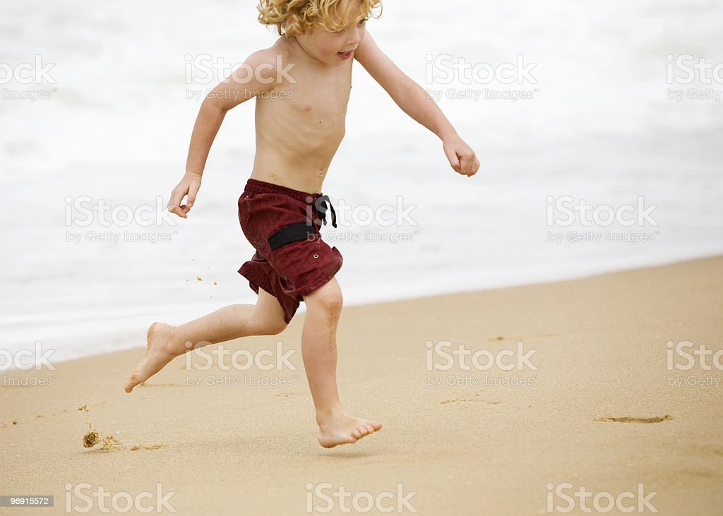 Young blonde boy near the surf royalty-free stock photo