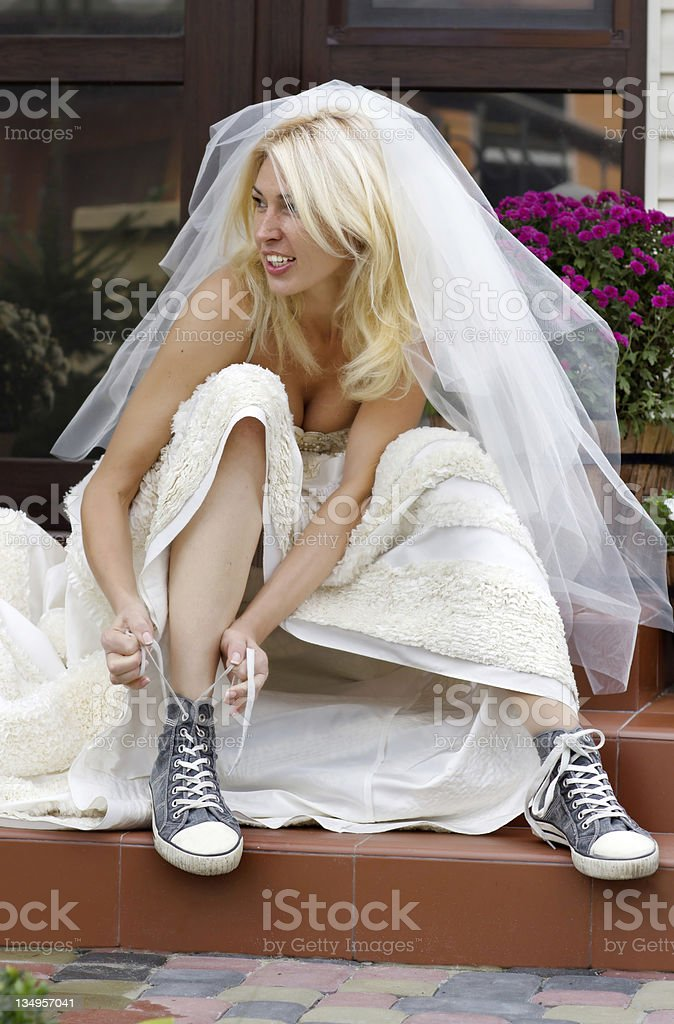 Young blonde bride sitting on step tying her shoe laces stock photo