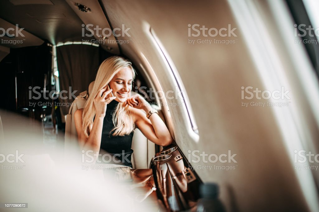 Young blonde businesswoman having a conversation on a smart phone while flying in a private jet stock photo