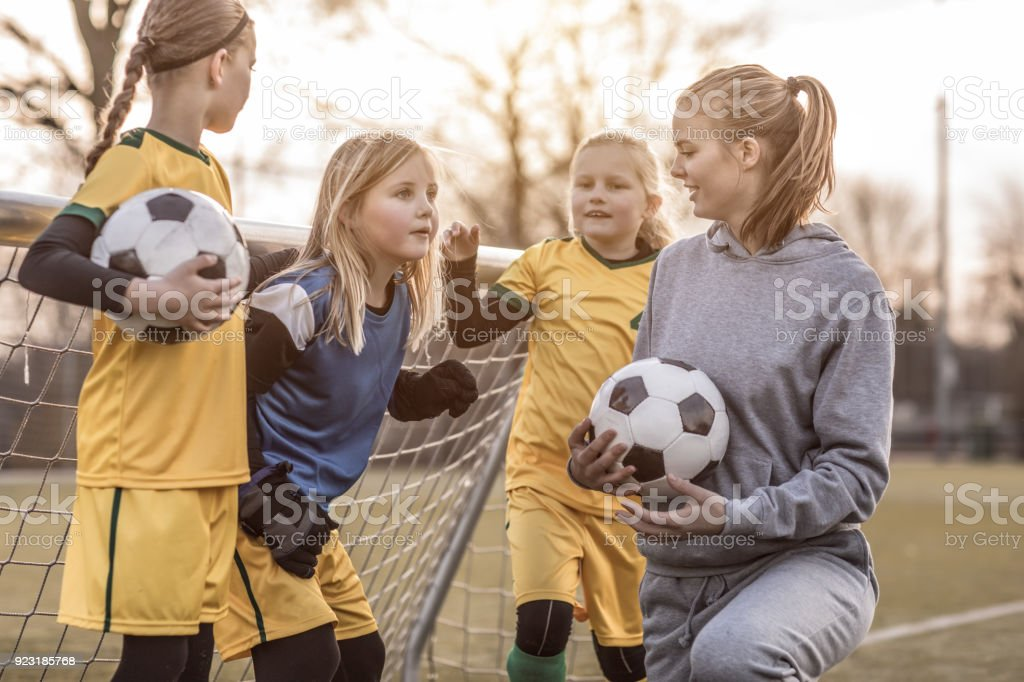 Young Blonde Female Soccer Coach and her Girl Football team