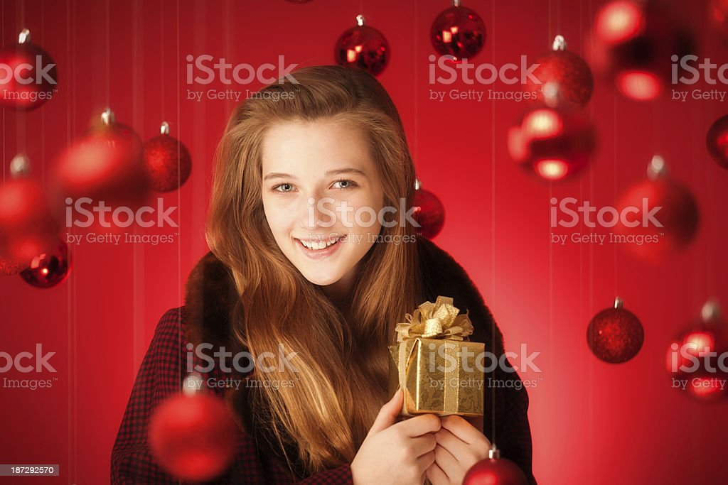 A Happy young woman celebrating Christmas with a small Christmas gift...