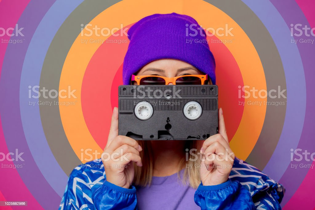 Young blonde girl in 90s sports jacket and hat stock photo