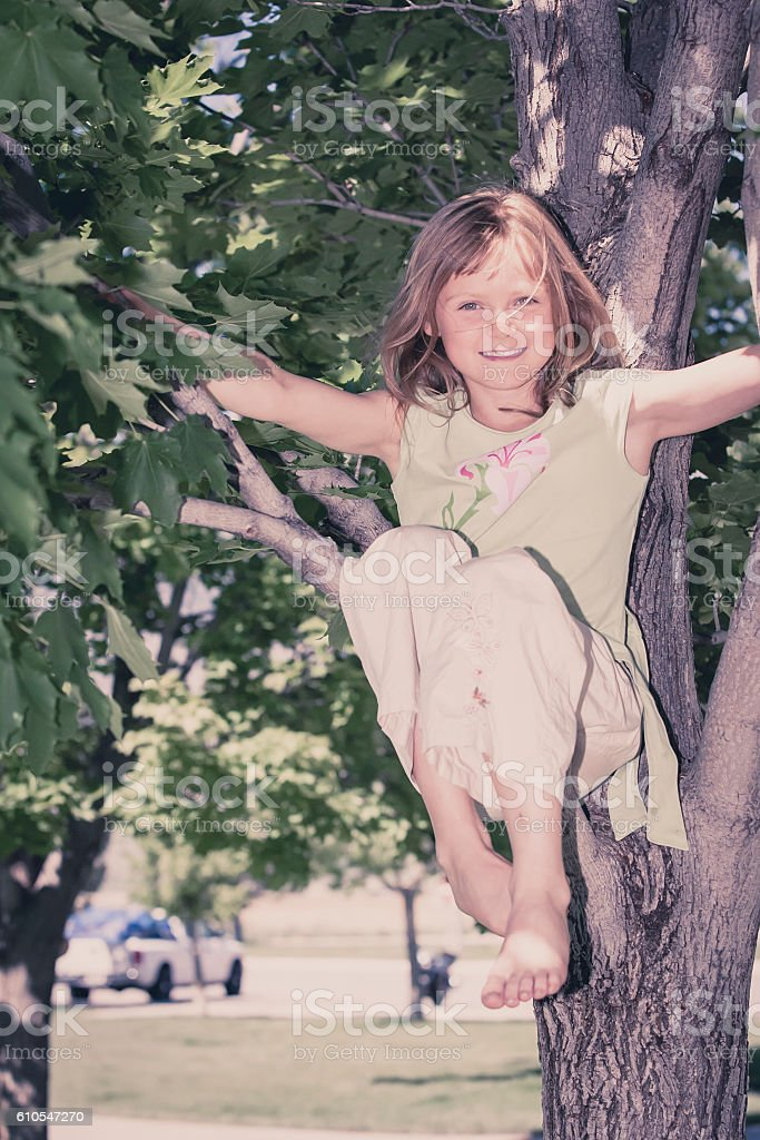 Young blonde girl in garden climbing tree stock photo