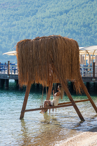 Turkey, Bodrum, October 2020. A young blonde girl is resting on a wooden swing above the water by the sea. A cozy place for rest and relaxation.