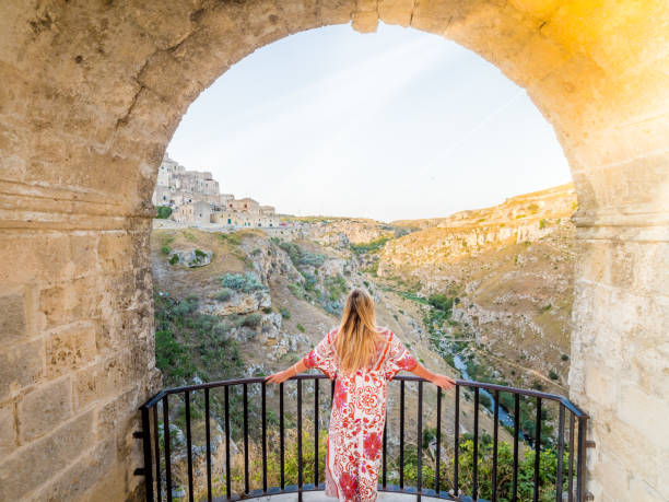Young blonde girl looking out over the  landscape of the Sassi di Matera Young blonde girl looking out over the  landscape of the Sassi di Matera, prehistoric historic center, UNESCO World Heritage Site, European Capital of Culture 2019 (wide) matera italy stock pictures, royalty-free photos & images