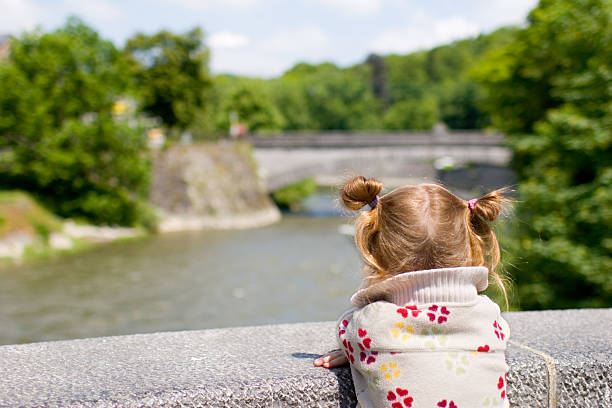 Young blonde girl on bridge, admiring the view stock photo