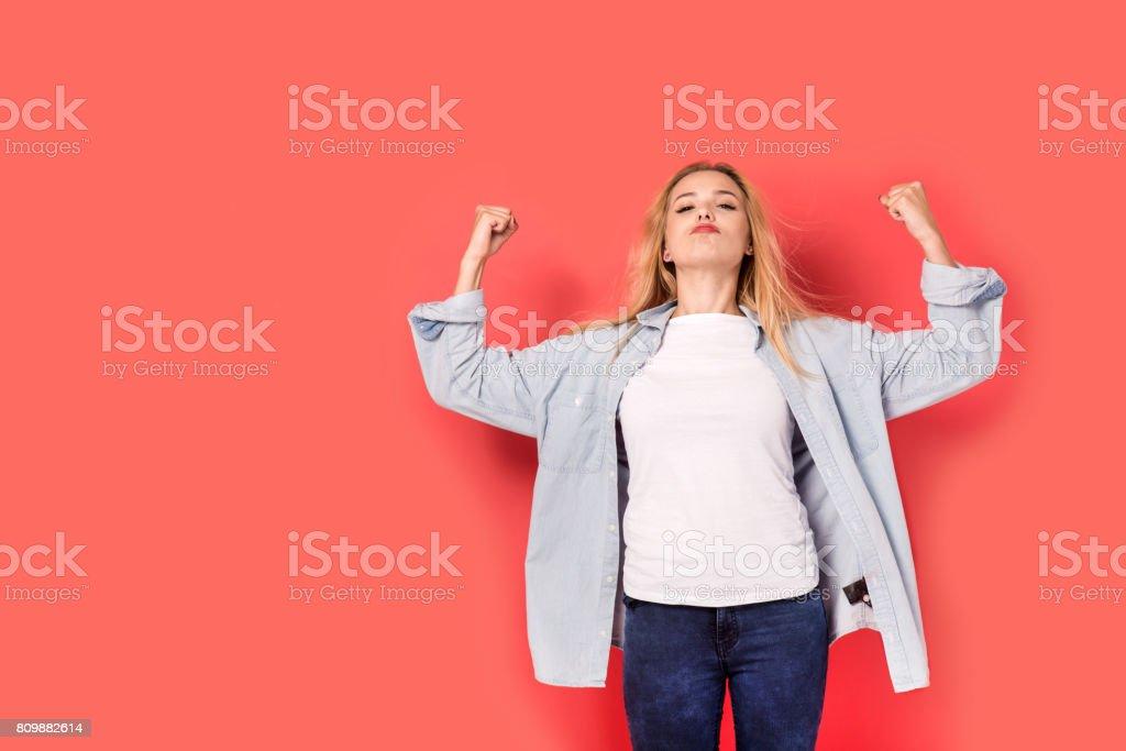 Jovem menina loira mostra sua força em fundo vermelho - foto de acervo