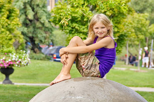 Young Blonde Girl Watching the Summer Day Pass stock photo