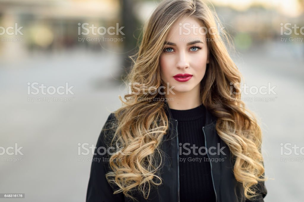 Young blonde girl with beautiful blue eyes wearing black jacket. stock photo