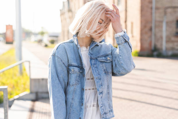 Young blonde girl with disheveled hair on a city street stock photo