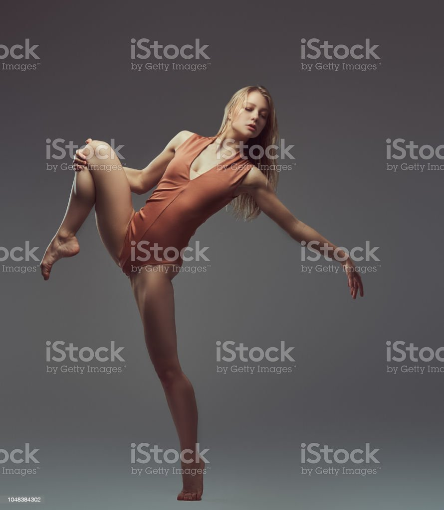 Young blonde graceful ballerina stretching and posing in a studio....