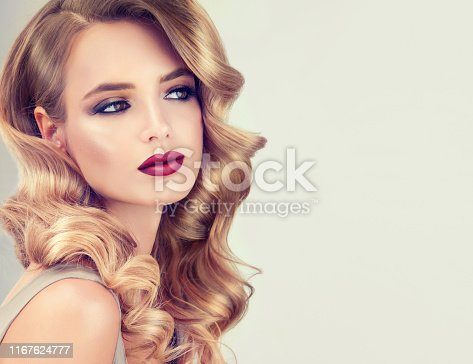 Young, blonde haired woman with elegant, voluminous evening hairstyle. Beautiful model with long, dense, curly hair and vivid makeup with red lipstick. Hairdressing art, hair care and beauty products.