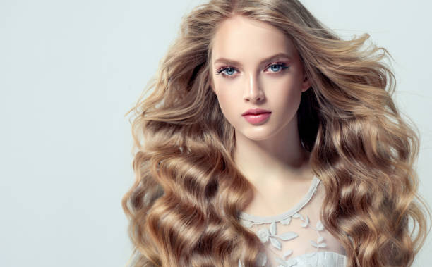 young, blonde haired beautiful model with long, wavy,well groomed hair. flying hair. - capelli mossi foto e immagini stock