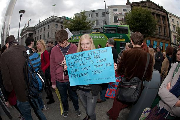 Young blonde holds hand made poster regarding abortion Dublin, Ireland - September 29, 2012: Dublin March for Choice 2012, Young blonde holds hand made poster regarding abortion while her male colleague use mobile phone pro choice stock pictures, royalty-free photos & images