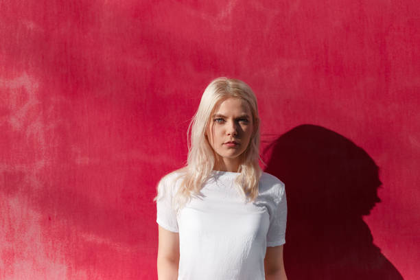 Young blonde in white t-shirt on red wall Portrait of pretty casual girl with fair hair wearing white t-shirt and looking at camera against red wall only young women stock pictures, royalty-free photos & images