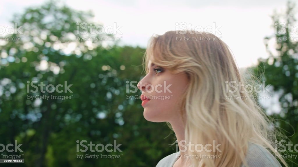 A Young Blonde Lady Turning Back her Head Outdoors stock photo