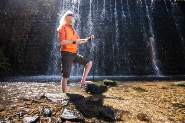 Young blonde man standing in front of a waterfall and posing for a camera stock photo