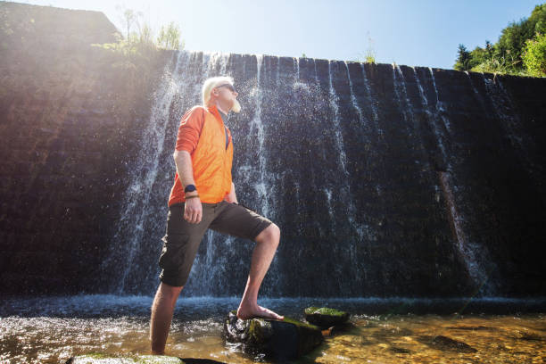 Young blonde man standing in front of a waterfall stock photo
