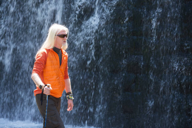 Young blonde man walking in front of a waterfall stock photo