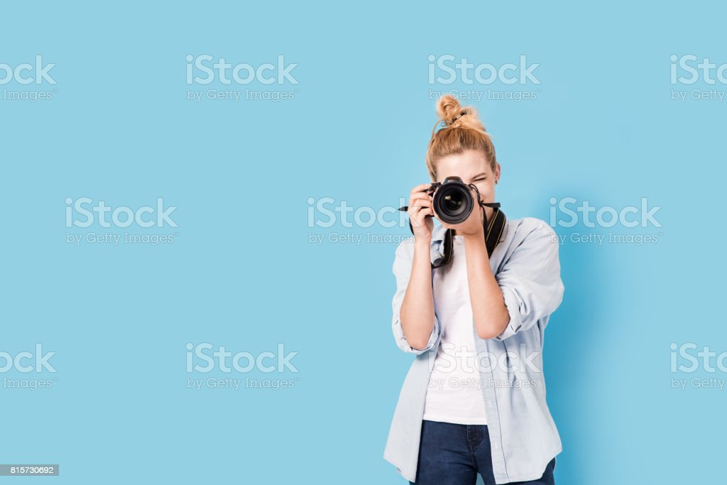 Young blonde photographer is taking a photo. Model isolated on a blue background with copy space – zdjęcie