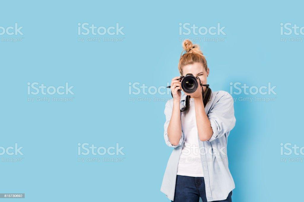 Jeune photographe blonde prend une photo. Isolé sur un fond bleu avec espace copie de modèle - Photo