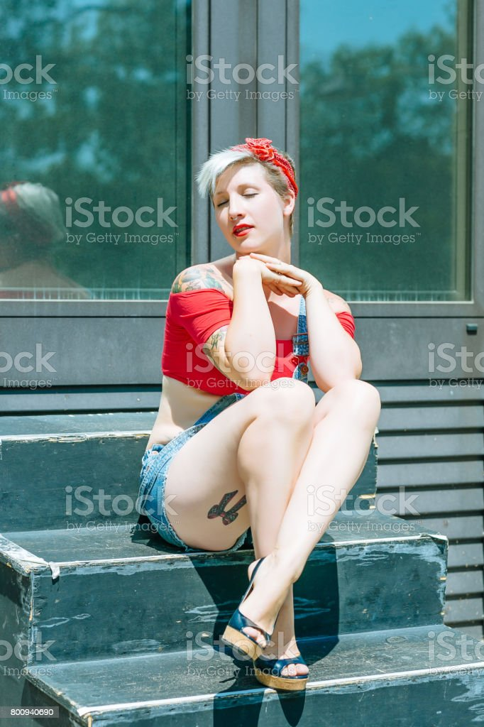 Young Blonde Pinup Girl With A Red Bow In Her Hair Sitting