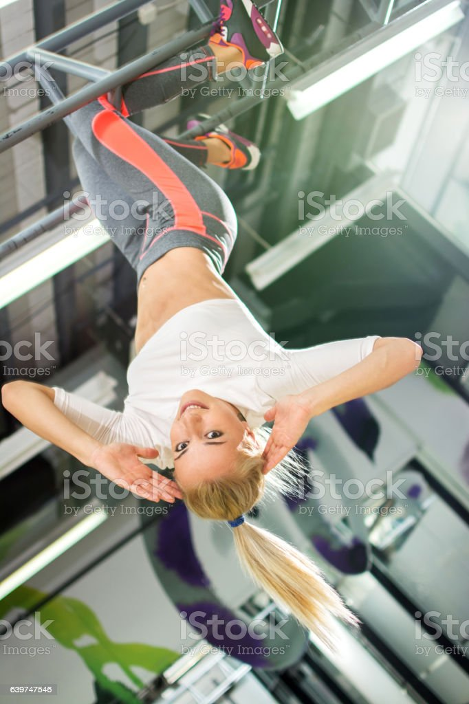 Young blonde sportswoman hanging upside down in a gym.