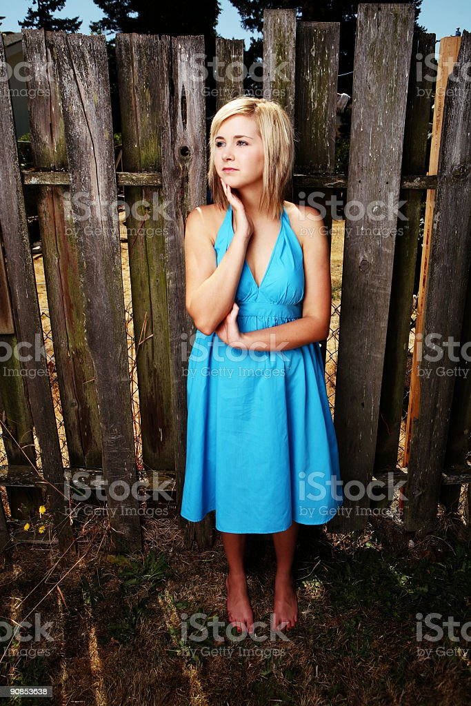 Young Blonde Touching her Face in Front of Fence royalty-free stock photo