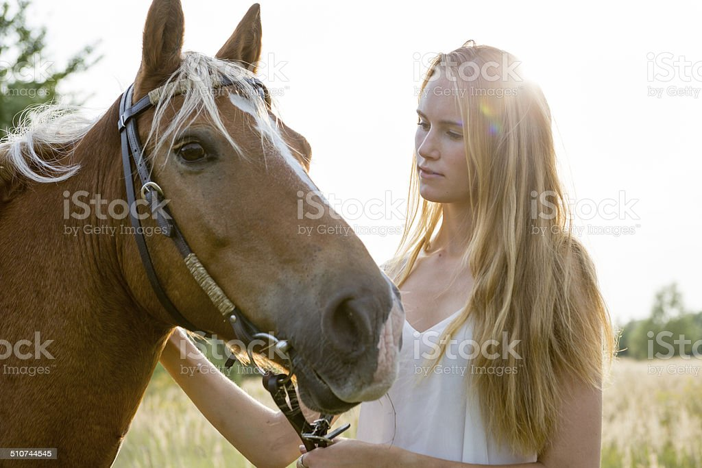 young blonde woman and her horse royalty-free stock photo