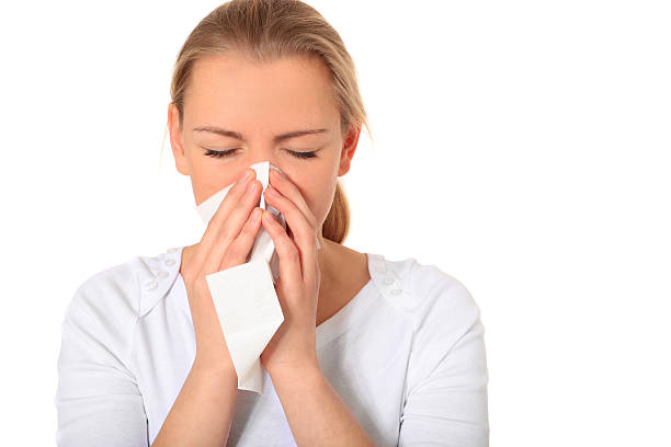 Young blonde woman blowing her nose with a tissue stock photo