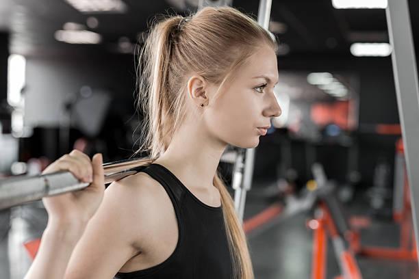 junge blondine frau übungen mit langhantel im fitnessraum - damen leggings übergrößen stock-fotos und bilder