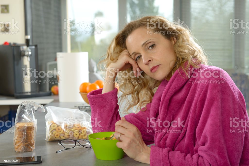 young blonde woman eating cereals in the morning royalty-free stock photo