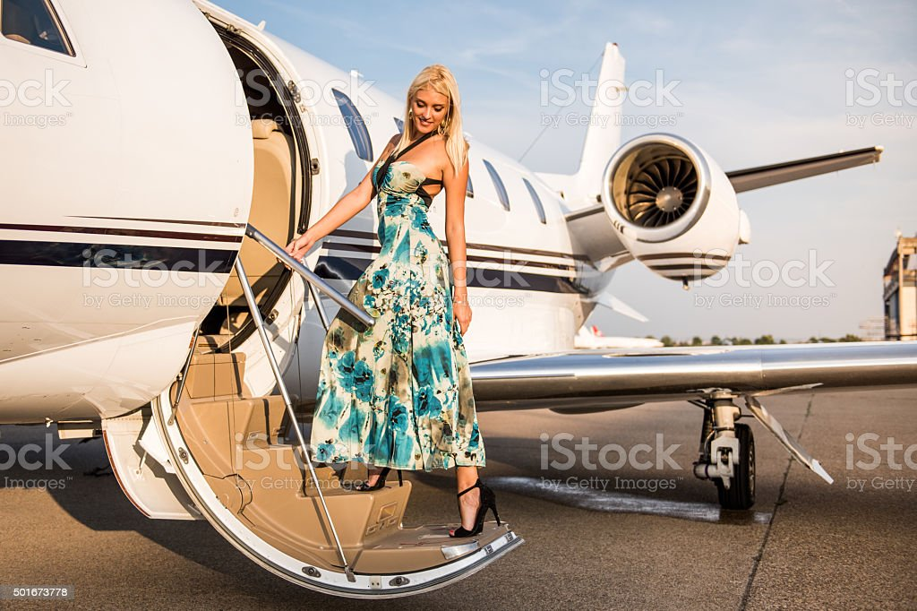 Young blonde woman entering private jet aeroplane stock photo