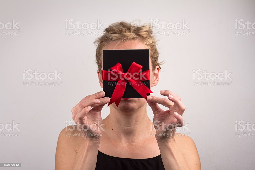 Young blonde woman holding a card with ribbon in front foto de stock royalty-free