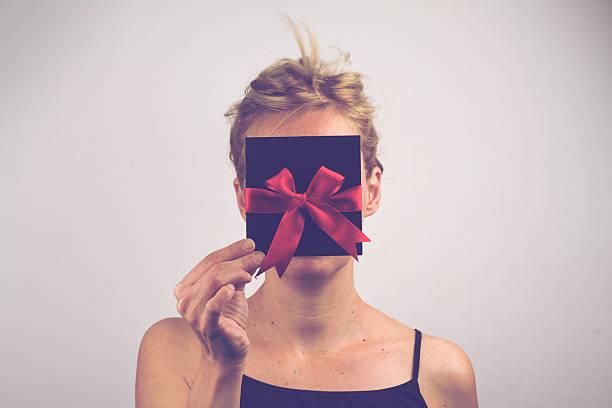 young blonde woman holding a card with ribbon in front - gutschein weihnachten stock-fotos und bilder