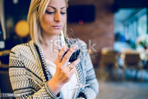 Young blonde woman holding a glass of red vine looking at beverage at party home or restaurant celebration holiday