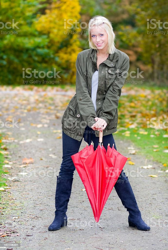 Young blonde Woman holding red umbrella in park portrait royalty-free stock photo