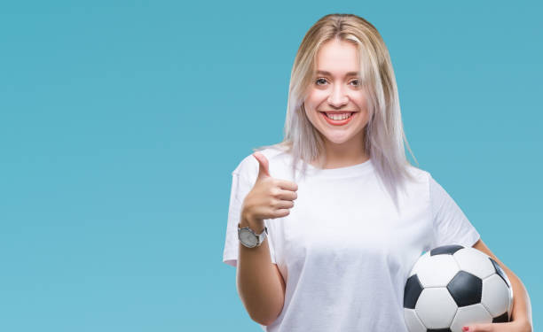 young blonde woman holding soccer football ball over isolated background happy with big smile doing ok sign, thumb up with fingers, excellent sign - soccer supporter portrait imagens e fotografias de stock
